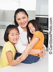 Smiling mother with her young daughters in kitchen