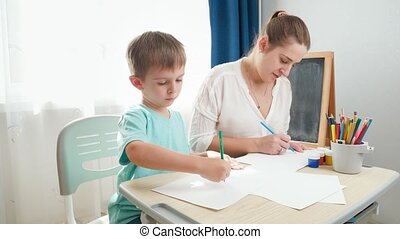 Smiling mother with little son drawing picture with pencil. Child sitting behind school desk and doing homework with parent. Education and remote school at home during lockdown and self isolation