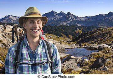 Smiling mountain guide with a backpack and walking stick on ...