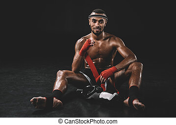 smiling muay thai fighter swathing hand in bandage isolated on black