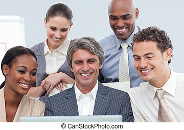 Smiling Multi-ethnic business group using a laptop