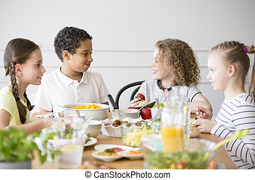 Smiling multicultural group of children eating food during birthday party