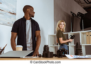 smiling multicultural photographers looking at each other before work in studio