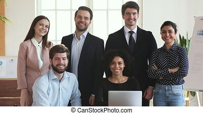 Smiling multiethnic business people group posing in office with laptop