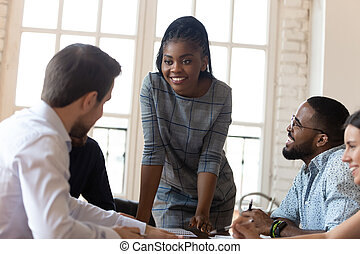 Smiling multiethnic colleagues discuss business ideas at ...