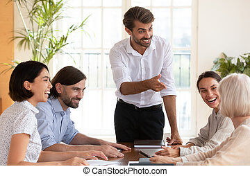 Smiling multiracial colleagues brainstorm at office meeting
