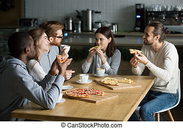 Smiling multiracial friends talking drinking coffee eating pizza