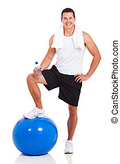 muscular man with water bottle and fitness ball