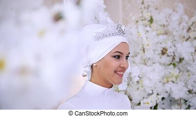 Smiling muslim bride with bridal make up in flowers, close...