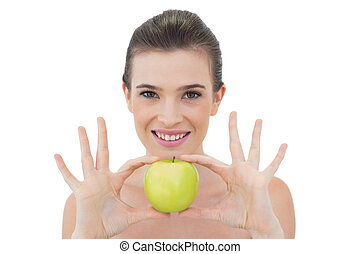 Smiling natural brown haired model holding an apple