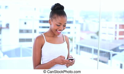 Smiling natural model sending a text message while posing