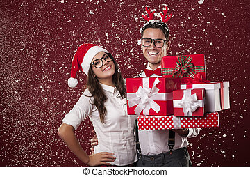 Smiling nerd couple with a lot of christmas presents during the snowing