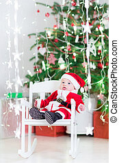 Smiling newborn baby boy in Santa costume sitting in a white roc