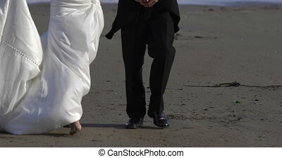 Smiling newlywed couple walking on the beach on their...