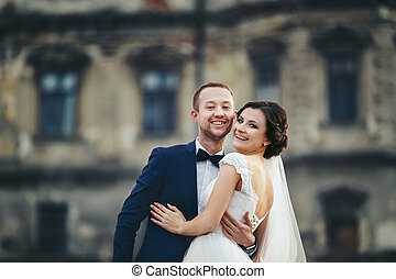 Smiling newlyweds hug in the front of an old castle