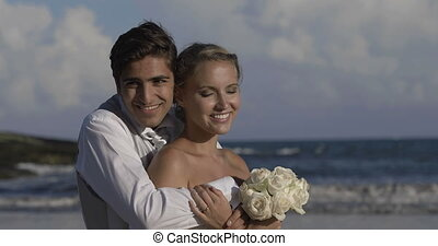 Smiling newlyweds hugging on the beach on their wedding day