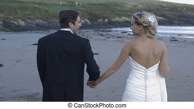 Smiling newlyweds walking on the beach on their wedding day