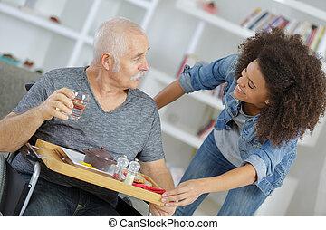 smiling nurse giving food to senior man at home