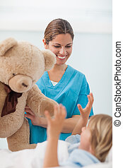 Smiling nurse showing a teddy bear to a child in hospital...