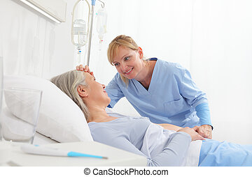 smiling nurse take comfort elderly woman lying in the hospital room bed, by stroking her, concept of loneliness and old age diseases