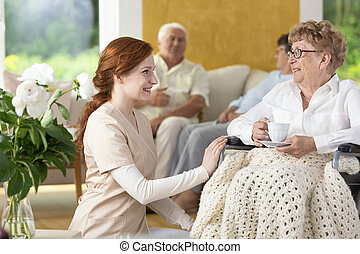 Smiling nurse taking care of disabled senior woman in the nursing house