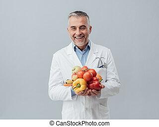 Smiling nutritionist holding fresh vegetables and fruit