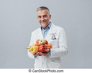 Smiling nutritionist holding fresh vegetables and fruit:...