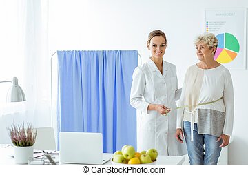 Smiling nutritionist measuring patient