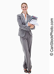 Smiling office employee with pile of paperwork against a...