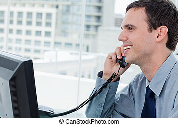 Smiling office worker on the phone
