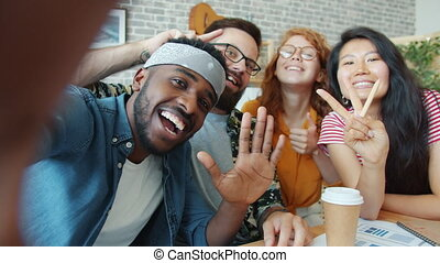 Smiling office workers multi-racial team taking selfie at work posing for camera holding device showing hand gestures. People and modern gadgets concept.