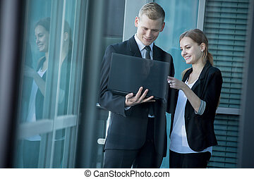 Smiling office workers using laptop