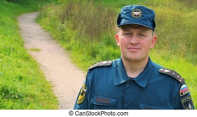 smiling officer of rescue service standing in park