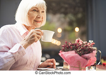 Smiling old lady drinking hot drink outside