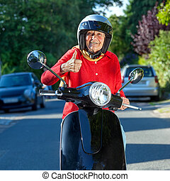 Smiling old lady on a scooter stopped in the street facing...