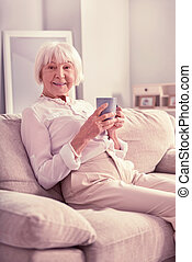 Smiling old lady sitting with cup of coffee