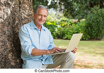 Smiling old man with a laptop