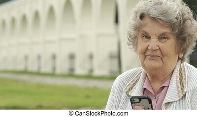 Smiling old woman holds silver smartphone outdoors - Smiling...