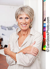 Smiling old woman posing with arms crossed