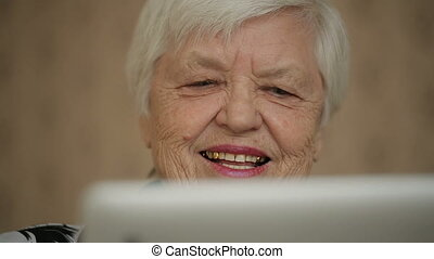 Smiling Old Woman Uses Tablet PC