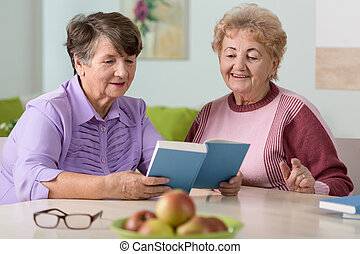 Smiling old women reading