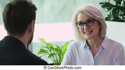Smiling friendly older businesswoman hr employer having business conversation with businessman job applicant client or partner discussing qualifications make good first impression at business meeting
