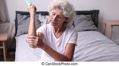 Smiling older woman applying cream on elbow sitting on bed...