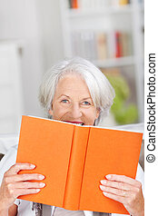 Smiling older woman hiding behind her book