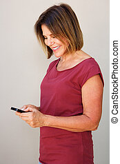 smiling older woman looking at cell phone