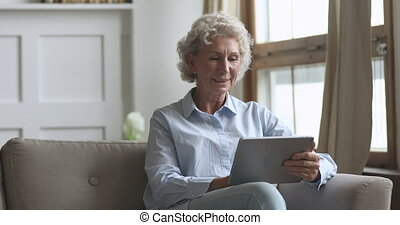 Smiling older woman sitting on comfortable couch, using digital tablet.