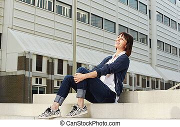 Smiling older woman sitting on steps in city