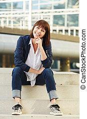 Smiling older woman sitting on steps outside