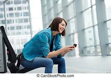 Smiling older woman sitting with mobile phone