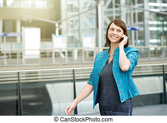 Smiling older woman walking with mobile phone